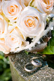 Wedding rings. A closeup of the weddings rings in white gold with three diamonds on the background of the bride bouquet with roses Royalty Free Stock Image