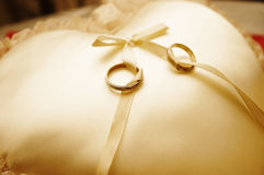 Wedding Rings. A pair of wedding rings on a golden pillow Royalty Free Stock Photo