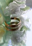 Wedding rings. Two wedding rings with satin roses Royalty Free Stock Photography