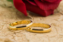 Wedding rings and artificial rose on brown background Royalty Free Stock Photography