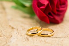 Wedding rings and artificial rose on brown background Stock Photos