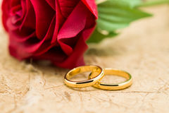 Wedding rings and artificial rose on brown background Royalty Free Stock Images