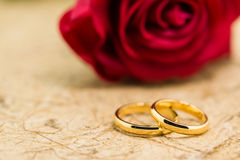 Wedding rings and artificial rose on brown background Royalty Free Stock Photo
