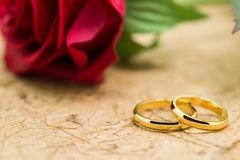Wedding rings and artificial rose on brown background Stock Photography