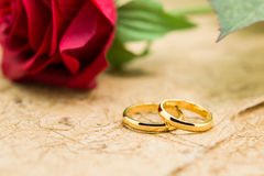 Wedding rings and artificial rose on brown background Stock Image