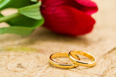 Wedding rings and artificial rose on brown background Royalty Free Stock Photos