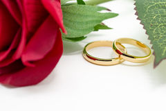 Wedding rings and artificial rose on white background Stock Images