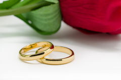 Wedding rings and artificial rose on white background Royalty Free Stock Photo