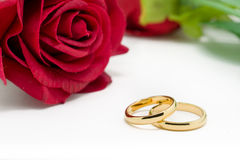 Wedding rings and artificial rose on white background Stock Photo