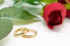 Wedding rings and artificial rose on white background Royalty Free Stock Photos