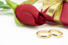 Wedding rings and artificial rose on white background Royalty Free Stock Images