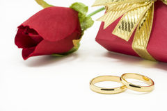 Wedding rings and artificial rose on white background Stock Photos