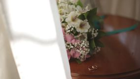 Wedding rings on a background of a bouquet of the bride. Wedding rings on background of a bouquet of the bride stock video footage