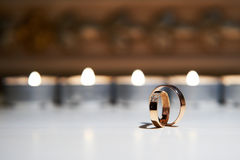 Wedding rings on a background of burning candles Royalty Free Stock Photography