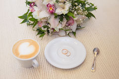 Wedding rings. On a background with a cup of coffee with a heart and a bridal bouquet Stock Photo