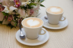 Wedding rings. On a background with a cup of coffee with a heart and a bridal bouquet Royalty Free Stock Photo