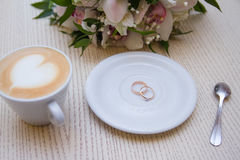 Wedding rings. On a background with a cup of coffee with a heart and a bridal bouquet Stock Images