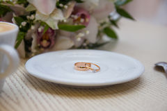 Wedding rings. On a background with a cup of coffee with a heart and a bridal bouquet Stock Photography