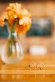 Wedding rings on a background of gerbera flower vases. Wedding j Stock Photos