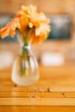 Wedding rings on a background of gerbera flower vases. Wedding j Royalty Free Stock Photo