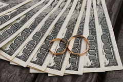 Wedding rings on the background of money.  Royalty Free Stock Image