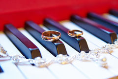 Wedding rings, background piano Stock Image