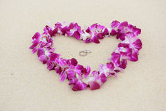 Wedding rings beach love concept. Closeup of two bands in flower heart for casual marriage celebration Stock Photo