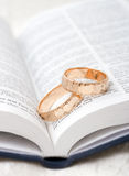Wedding rings on a bible. Pair of gold wedding bands Stock Photos