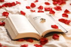 Wedding Rings On The Bible. Rings On The Bible; Wedding Rings On The New Testament Bible Surrounded By Rose Petals Royalty Free Stock Photos