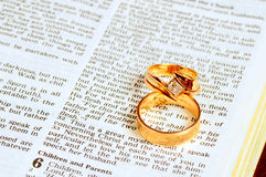 Wedding rings on Bible. Two gold wedding rings rest atop the marriage passage from Ephesians 5 in the Bible Royalty Free Stock Photo