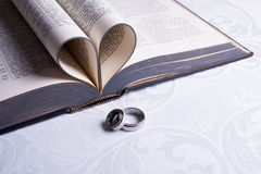 Wedding Rings and Bible. Two wedding rings with Hebrew on them and an open Afrikaans Bible with pages folded in a heart Stock Image