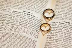 Wedding rings on a bible. The shadows of of two wedding rings form hearts on the pages of a bible Royalty Free Stock Image