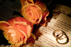 Wedding rings on a bible with the Genesis text Royalty Free Stock Image