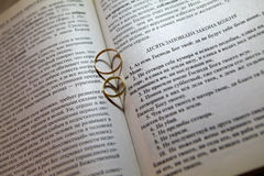 Wedding rings on Bible. Wedding rings with hearts shadow on Bible Royalty Free Stock Photos