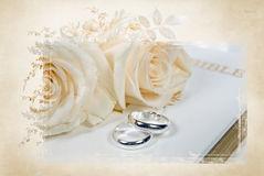 Wedding rings on Bible. Pair of silver wedding rings and rose bouquet on Holy Bible with elegant floral mask frame Stock Images