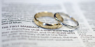 Wedding rings on Bible scripture Royalty Free Stock Photo