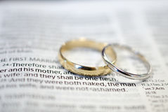 Wedding rings on Bible scripture Stock Photo
