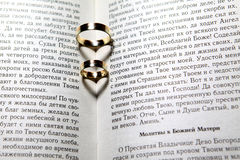 Wedding rings in Bible. Wedding rings with shadows like hearts in Bible Royalty Free Stock Image