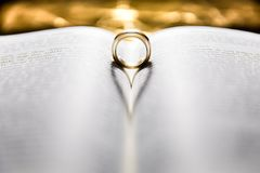Wedding Rings in the Bible. Forming a heart with gold backround Stock Images