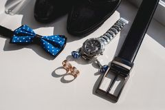 Wedding rings. Black leather shoes, watch, blue bow tie and cufflinks, on a white window sill. Accessory for formal dress. Symbol of elegance and fashion for Stock Photo