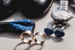 Wedding rings. Black leather shoes, watch, blue bow tie and cufflinks, on a white window sill. royalty free stock photos