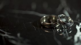 Wedding rings on a black marble stone table. Two rings on a black marble table.  stock video footage