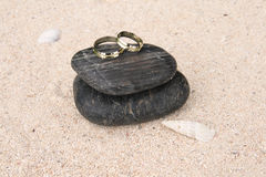 Wedding rings on black pebbles Royalty Free Stock Photos