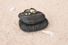 Wedding rings on black pebbles Royalty Free Stock Photos
