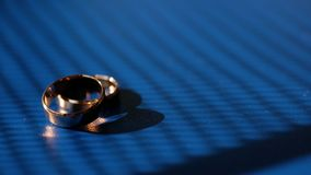 Wedding rings on blue background. Close-up. Wedding rings on blue background stock video footage