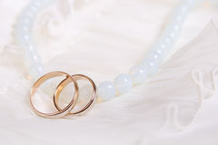 Wedding rings and blue beads Stock Photos
