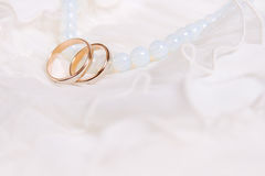 Wedding rings and blue beads. On lace light background royalty free stock photo