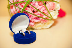 Wedding rings in the blue box on the background of the bride's b Royalty Free Stock Photo