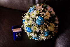Wedding rings in a blue box, a bridal bouquet of white flowers and blue roses Royalty Free Stock Photos