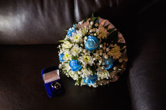 Wedding rings in a blue box, a bridal bouquet of white flowers Stock Images